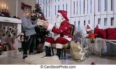 Santa Gives a Gift to a Boy in a Grey Box with Red Ribbon