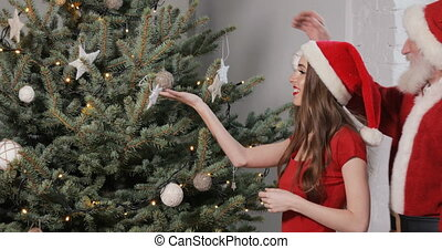 Santa Hangs Ornament on Christmas Tree - Caring santa...
