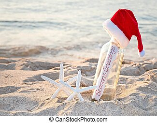 Santa hat on message in bottle with starfish