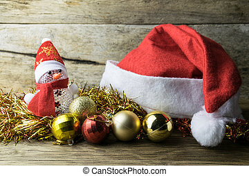 Santa Hat with Christmas decorations on old wooden background.