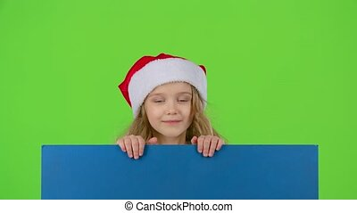 Santa helper jumps out from behind the blue board and shows a thumbs up. Green screen