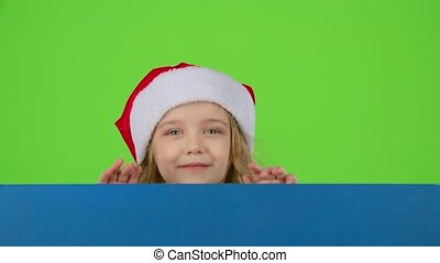 Santa helper looks out from behind a blue board and winks. Green screen