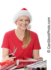 Santa helper - Young blond woman in santa hat packing...