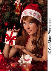 Santa helper with present under Christmas tree