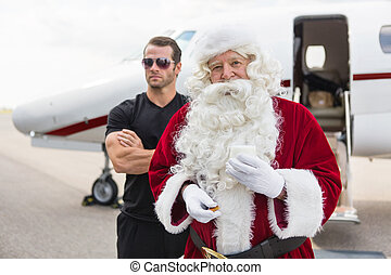 Santa Holding Milk Glass By Bodyguard Against Private Jet