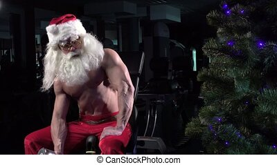 Santa in a gym training biceps near the Christmas tree