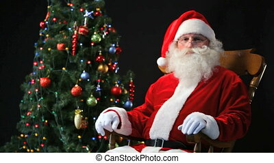Santa in a rocking-chair - Santa Claus sitting in a...