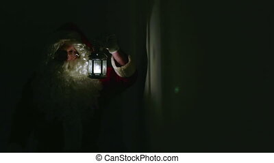 Santa In Dark - Santa Claus with a lantern making his way...
