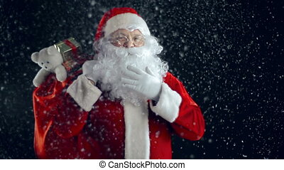 Santa in Snow - Santa Claus standing with sackful of gifts...