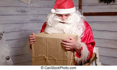 Santa is holding a big gift box in his hand