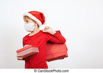 Santa kid wears protected face mask. Cute boy with christmas gifts. Christmas holidays during coronavirus quarantine.