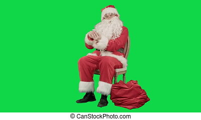 Santa laughing out loud as he talks on his cell phone on a...