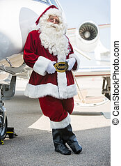 Santa Leaning On Private Jet At Airport Terminal