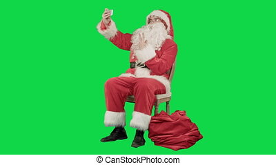 Santa makes selfie with smartphone on a Green Screen Chrome Key