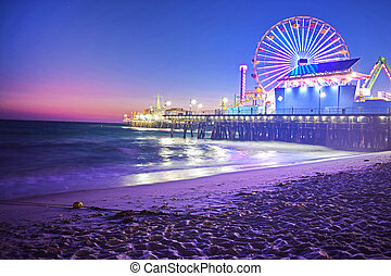 Santa Monica Pier and Ferris Wheel at night showing off all of the beautiful colored lights. Santa Monica is a city within Los Angeles, California.