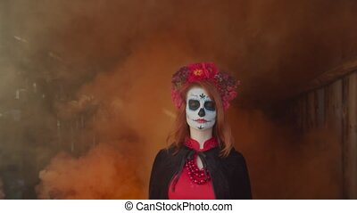 Mysterious santa muerte with sugar skull and colorful wreath appearing from clouds of orange smoke in rustic shed, looking with cold stare while guiding souls of deceased to afterlife on halloween.