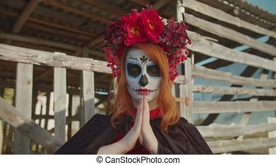 Spooky santa muerte in colorful wreath, lady of dead, standing with hands folded in prayer near rustic shed in countryside, praying for souls of deceased and safe delivery to afterlife.