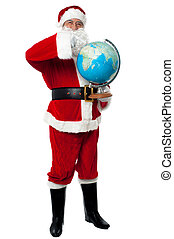 Santa pointing out a continent on globe. Full length studo...