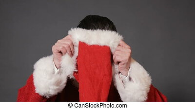 Intelligent old santa putting on red christmas hat, getting ready for the busiest time of the year