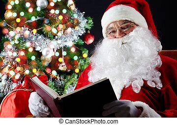 Santa reading a book - Santa sitting at the Christmas tree...
