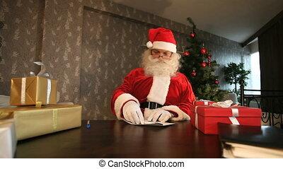 Santa reading letter sent him by kids