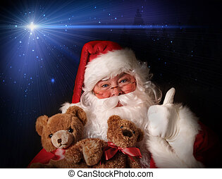 Santa smiling holding toy teddy bears in his arms aginst a...
