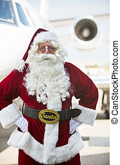 Santa Standing With Hands On Hip Against Private Jet
