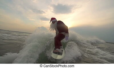 Santa Surfboarding - Sportive Santa Claus balancing on waves...