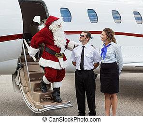 Santa thanking pilot and airhostess while disembarking private jet at airport terminal