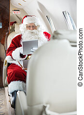 Santa Using Tablet Computer In Private Jet