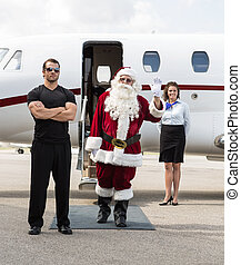 Santa Waving Hand Against Private Jet