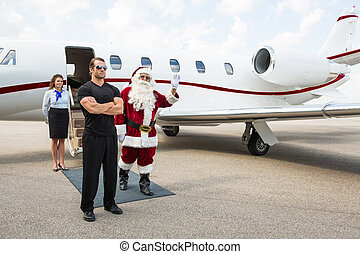 Santa waving hand with bodyguard and airhostess standing against private jet