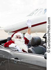 Santa Waving Hand In Convertible Against Private Jet