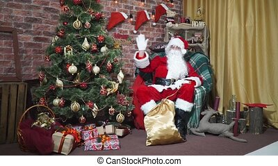 Santa waving his hand while sitting in a chair at the Christmas tree