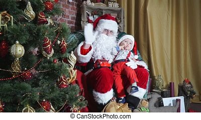 Santa waving until the child sitting on his lap cute smiles
