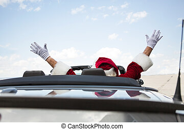 Santa With Arms Raised In Convertible Against Sky - Rear...