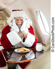 Santa With Cookies And Milk Sitting In Private Jet