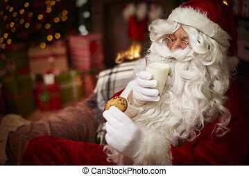 Santa with glass of milk and sweet biscuit