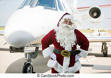 Santa With Hands On Hip Against Private Jet
