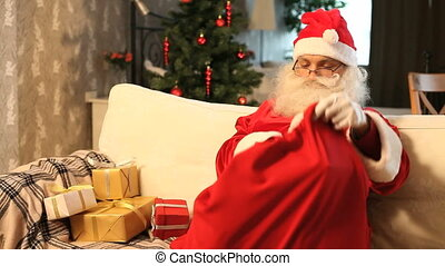 Santa with presents - Santa putting presents into his sack