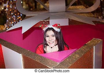 Santa woman dressing in a large gift box.