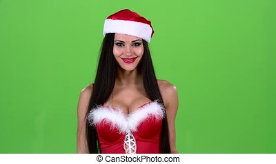 Santa woman holds a map in her hand and shows a thumb up. Green screen