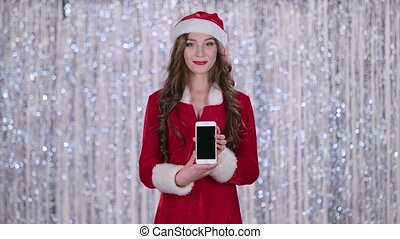 Santa woman holds the phone in her hands and looks into the distance. Bokeh background. Slow motion