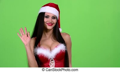 Santa woman in a New Year costume walks along the road and waves her hand. Green screen