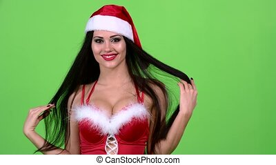 Santa woman in a sexy suit is walking down the road and...