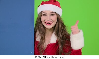 Santa woman looks out of the blue board and shows a thumbs up. Green screen. Close up