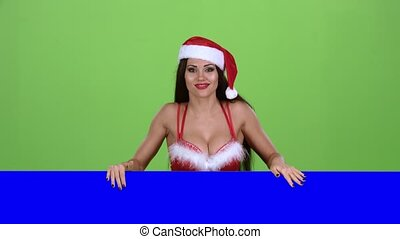 Santa woman looks out of the blue board and shows a thumbs up. Green screen. Slow motion