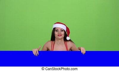 Santa woman looks out of the blue board and shows a thumbs...