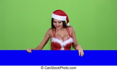 Santa woman peeking out from behind a blue board and showing...