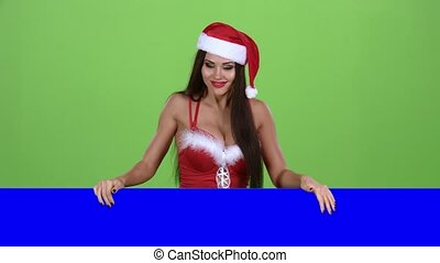 Santa woman peeking out from behind a blue board. Green...